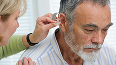Woman fitting a hearing aid in male patients ear
